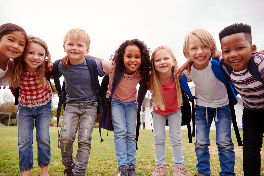 Diverse group of elementary-aged students donning backpacks and big smiles on a grassy field