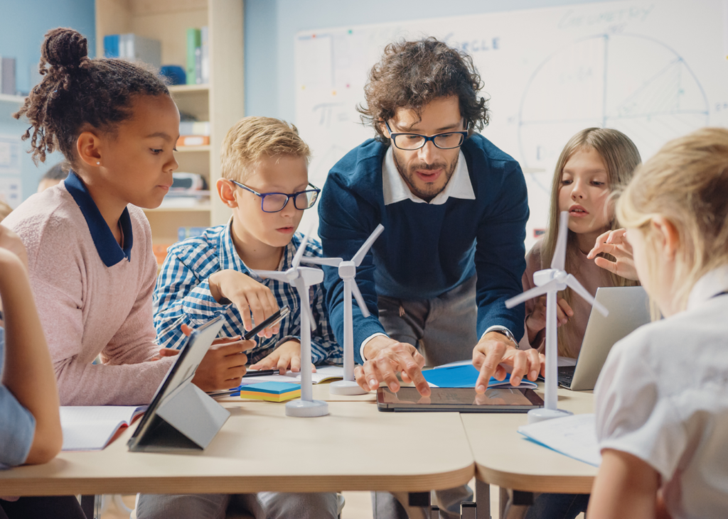 Educator inspiring a group of student with high tech model windmills controlled by a tablet
